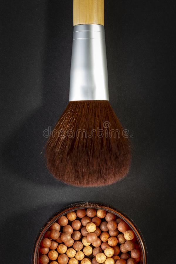 Make up brush and bronzer. Table top shot of face powder pearls in an open powder box and a make up brush. Feminine cosmetics and make up product, bronzer and royalty free stock images