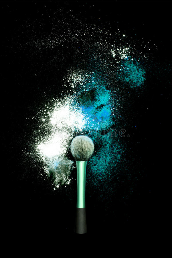 Make-up brush with colorful powder on black background. Explosion stars dust with bright colors. White and turquoise powder. royalty free stock images