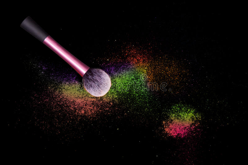 Make-up brush with colorful powder spilled glitter dust on black background. Makeup brush on new year`s Party with bright colors. stock photo