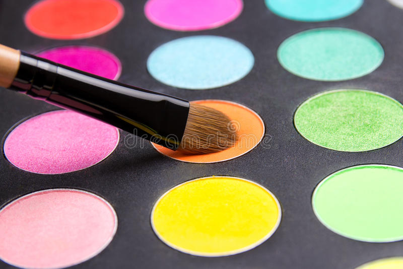 Make-up brush and eyeshadow palette close up. Make-up brush and eyeshadow palette over black close up royalty free stock photography