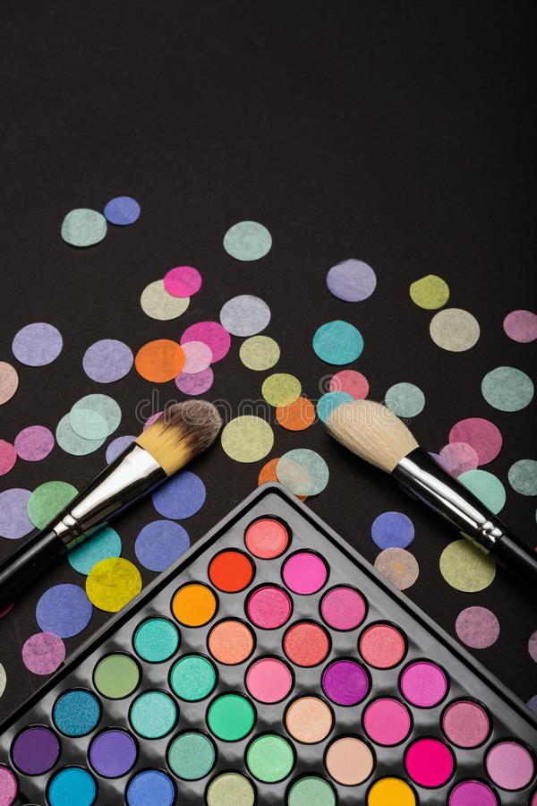 Make-up brush on the make-up palette with colorful confetti on black background. Flat lay. Top view stock photo