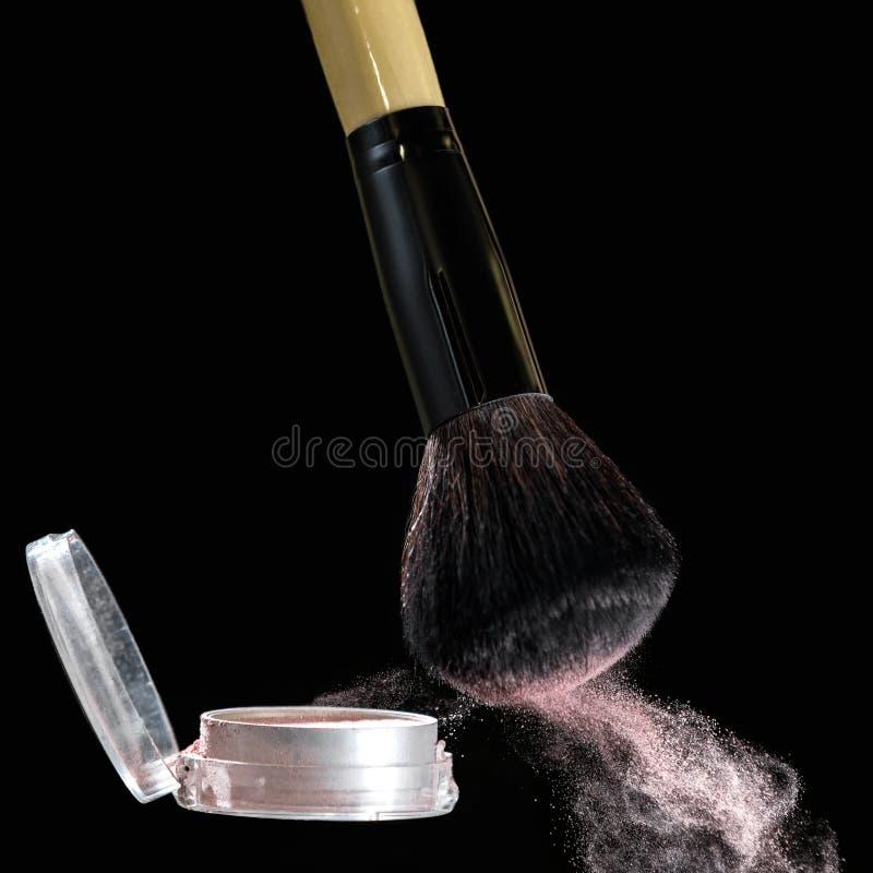 Make up brush with powder splashes on black background. Make up brush with pink powder splashes on black background. pink powder explosion royalty free stock photography
