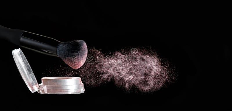Make up brush with powder splashes on black background. Make up brush with pink powder splashes on black background. pink powder explosion royalty free stock image