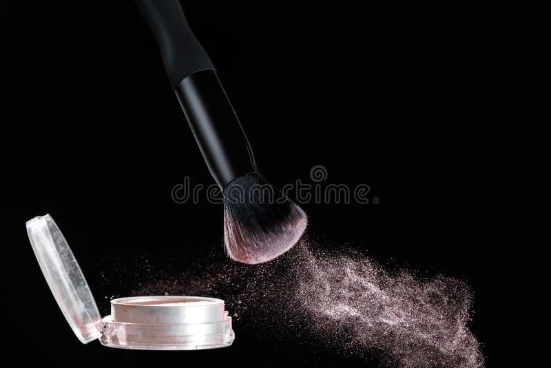 Make up brush with powder splashes on black background. Make up brush with pink powder splashes on black background. pink powder explosion stock photo