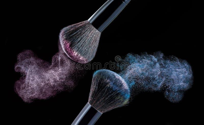 Make up brush with powder splashes on black background. Make up brush with pink and blue powder splashes on black background. pink powder explosion stock photography