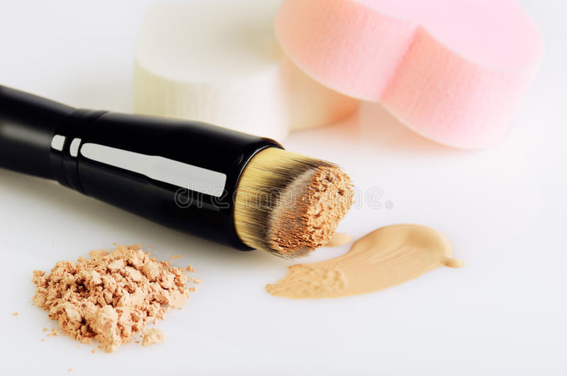 Make-up brush, sponges, smear makeup base and face powder on a w. Hite background, horizontal orientation stock photos