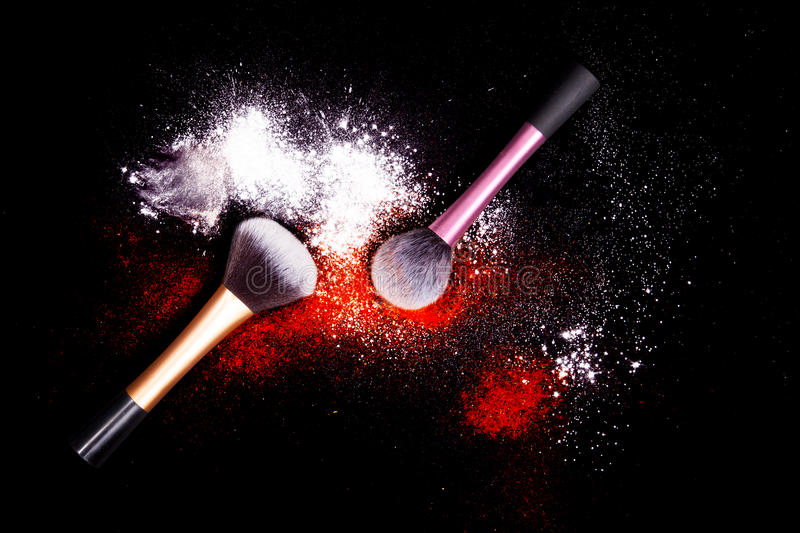 Make-up brush with white powder spilled glitter dust on black background. Makeup brush on new year`s Party with bright colors. Make-up brushes with colorful royalty free stock photo