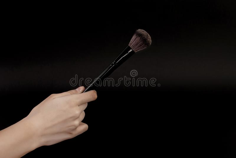 Make up brush in woman hand isolated on black background. Close up Make up and Female beauty image concept royalty free stock images