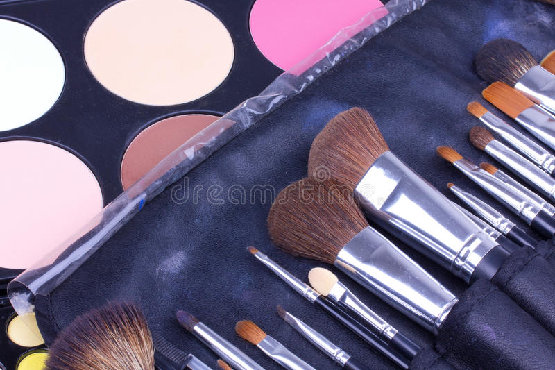 Make-up brushes in case on eyeshadows palettes stock photography
