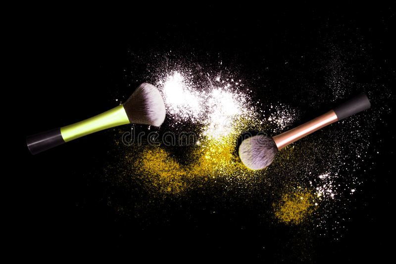 Make-up brushes with colorful powder spilled glitter dust on black background. stock images
