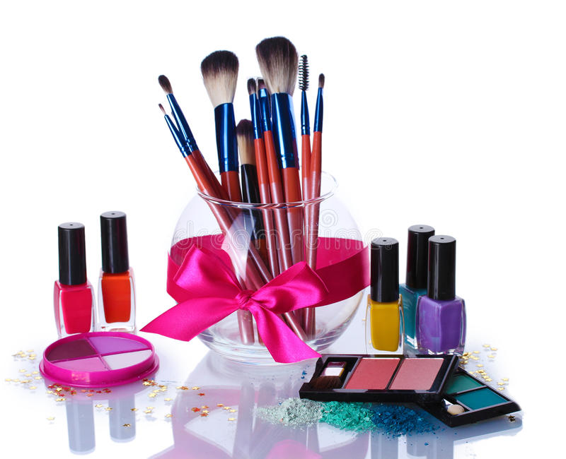 Make-up brushes in glass vase and cosmetics. Over the white stock photos