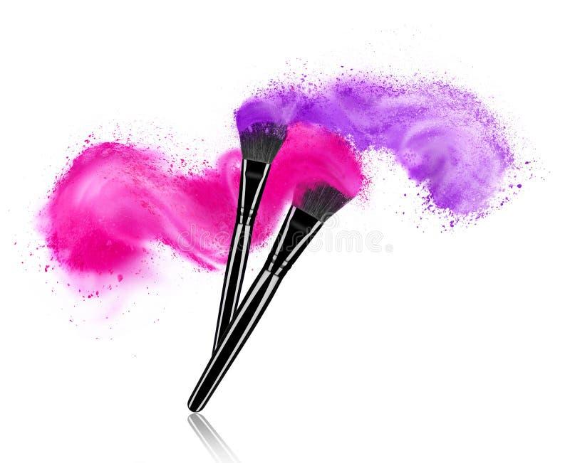 Make up brushes with powder splashes isolated on white royalty free stock photo
