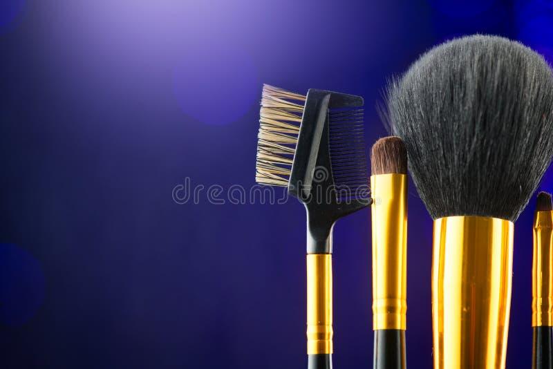 Make-up Brushes set over black holiday blinking background. Various Professional makeup brush on dark backdrop in studio. Make up artist tool stock images