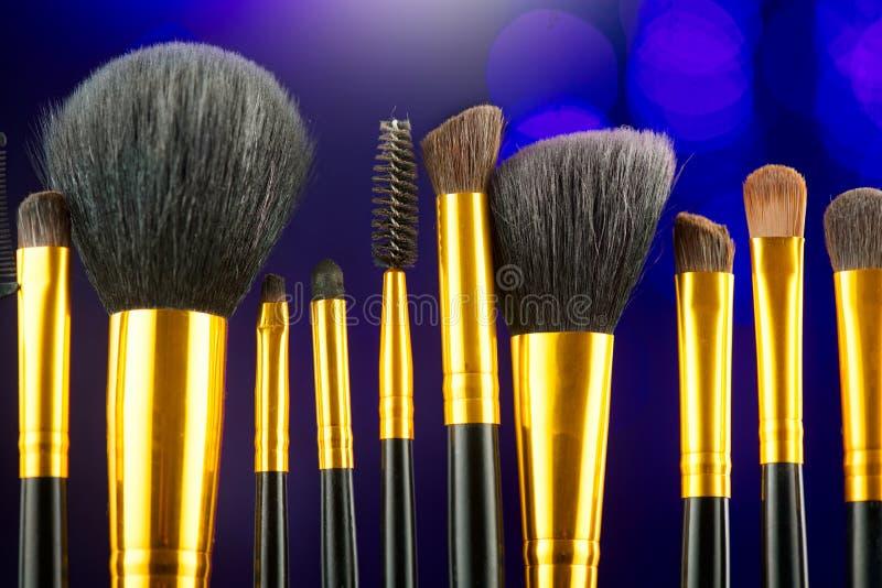 Make-up Brushes set over black holiday blinking background. Various Professional makeup brush on dark backdrop in studio. Make up artist tool royalty free stock photo