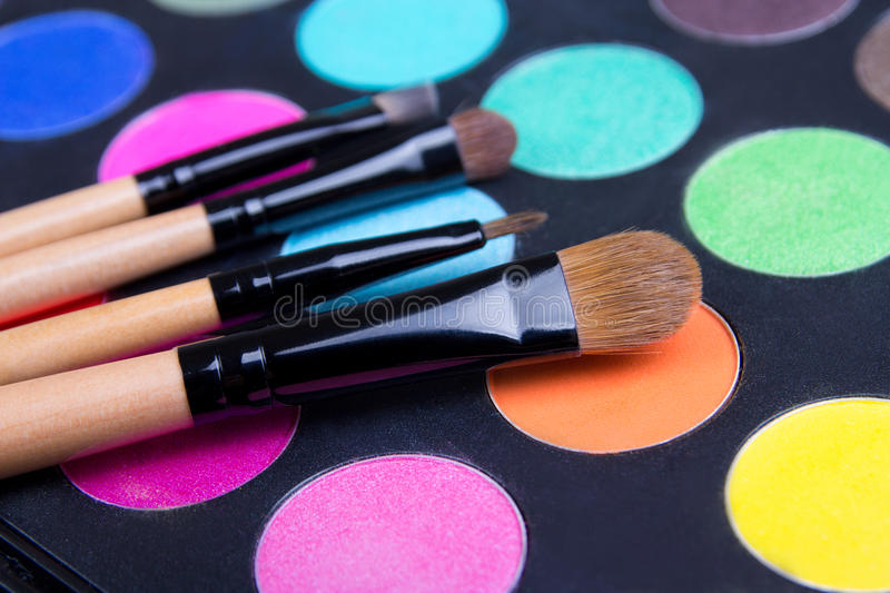 Make-up colorful eyeshadow palette and brushes. Over black royalty free stock photos