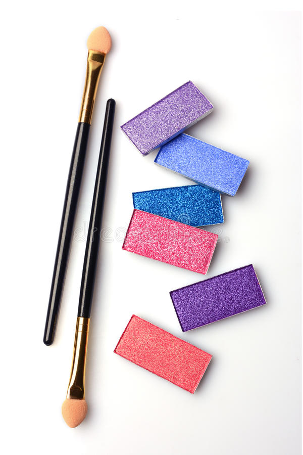 Make-up colorful shiny eyeshadow and applicator. On white stock image