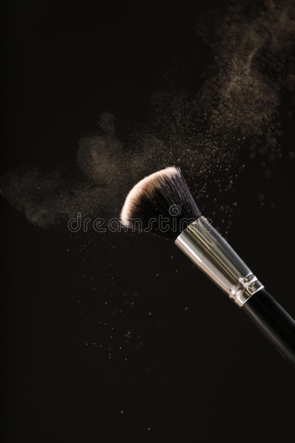 Make up cosmetic brushes with powder blush explosion on black background. Skin care or fashion concept stock image