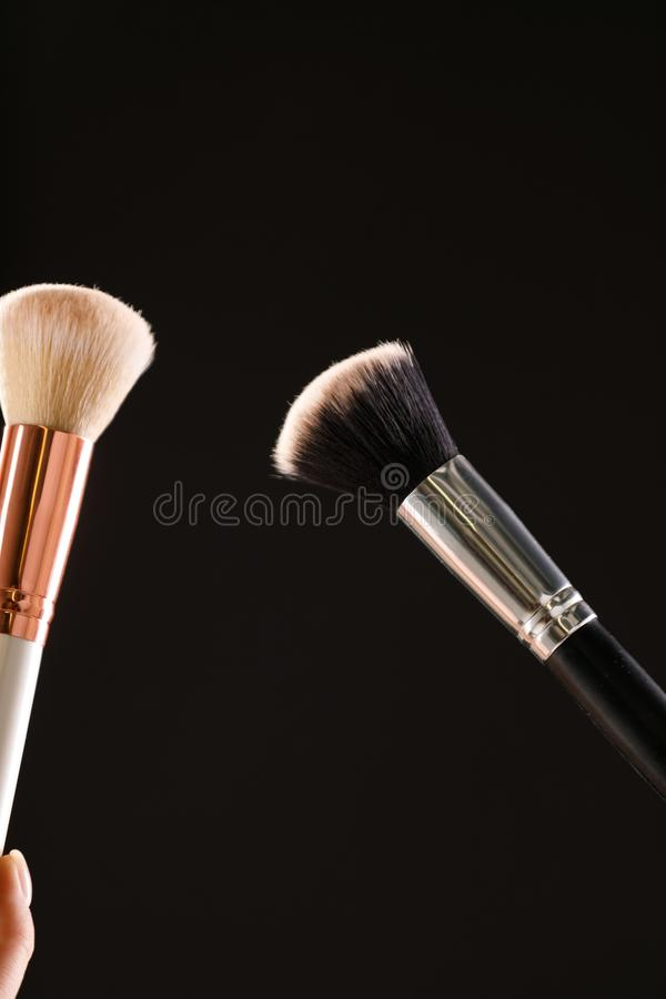 Make up cosmetic brushes with powder blush explosion on black background royalty free stock photo