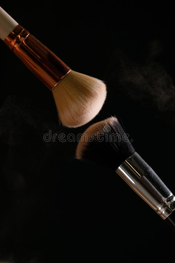 Make up cosmetic brushes with powder blush explosion on black background. Skin care or fashion concept stock images