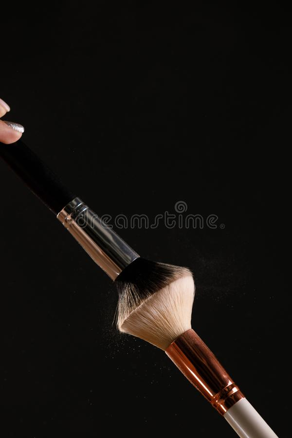 Make up cosmetic brushes with powder blush explosion on black background. Skin care or fashion concept royalty free stock photography