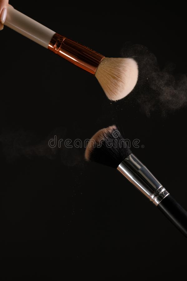 Make up cosmetic brushes with powder blush explosion on black background. Skin care or fashion concept royalty free stock image