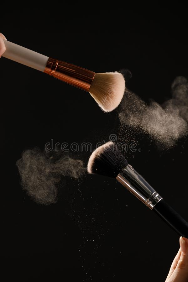 Make up cosmetic brushes with powder blush explosion on black background. Skin care or fashion concept royalty free stock photos