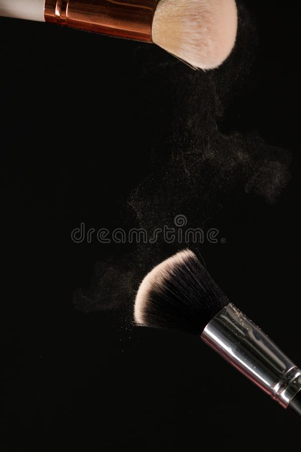 Make up cosmetic brushes with powder blush explosion on black background. Skin care or fashion concept royalty free stock photo