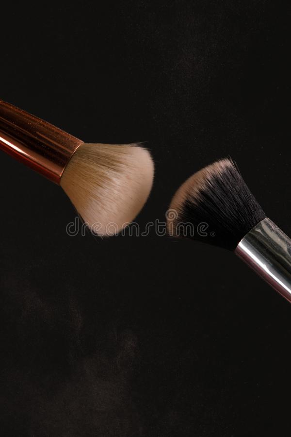 Make up cosmetic brushes with powder blush explosion on black background. Skin care or fashion concept royalty free stock images