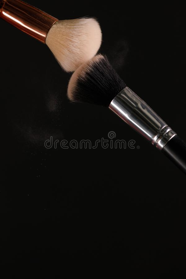 Make up cosmetic brushes with powder blush explosion on black background. Skin care or fashion concept stock photography