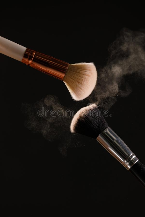 Make up cosmetic brushes with powder blush explosion on black background. Skin care or fashion concept stock photos