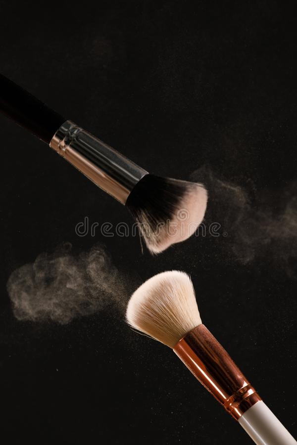 Make up cosmetic brushes with powder blush explosion on black background. Skin care or fashion concept stock photo