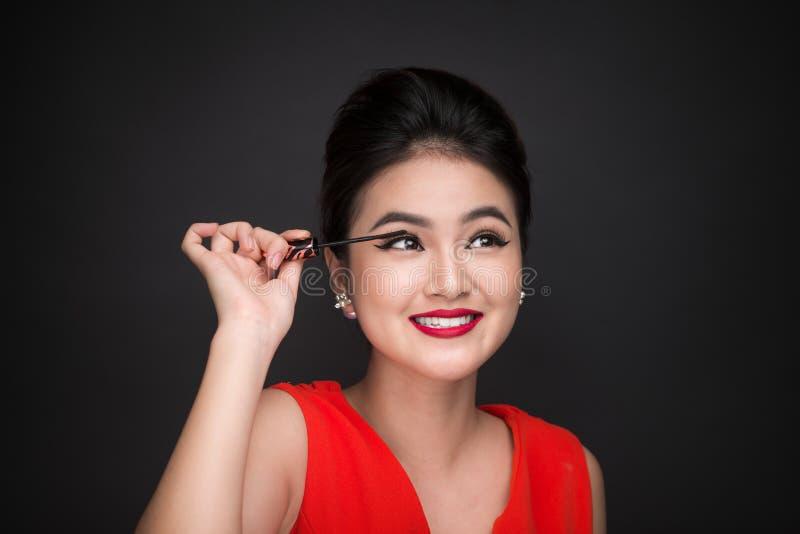 Make-up and cosmetics concept. Asian woman doing her makeup eyelashes black mascara. royalty free stock photo