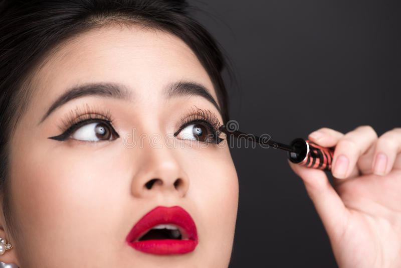 Make-up and cosmetics concept. Asian woman doing her makeup eyelashes black mascara. stock images