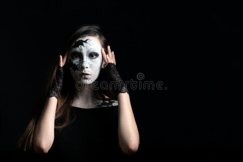 Make-up in de stijl van Halloween Een jong mooi meisje met geschilderde barsten op haar gezicht houdt vingers van haar tempels di stock foto's
