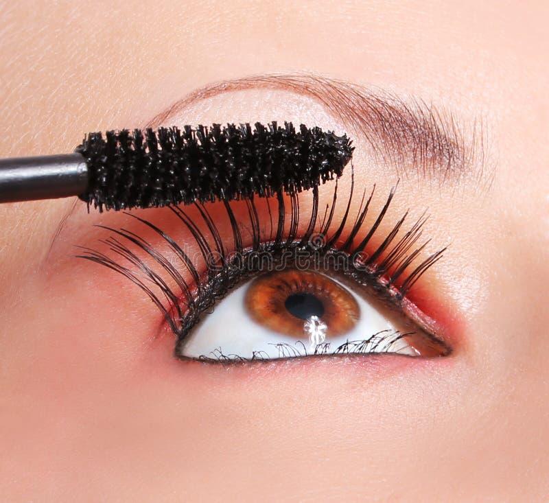 Make-up, die mascara, oog met lange wimpers toepassen stock afbeeldingen