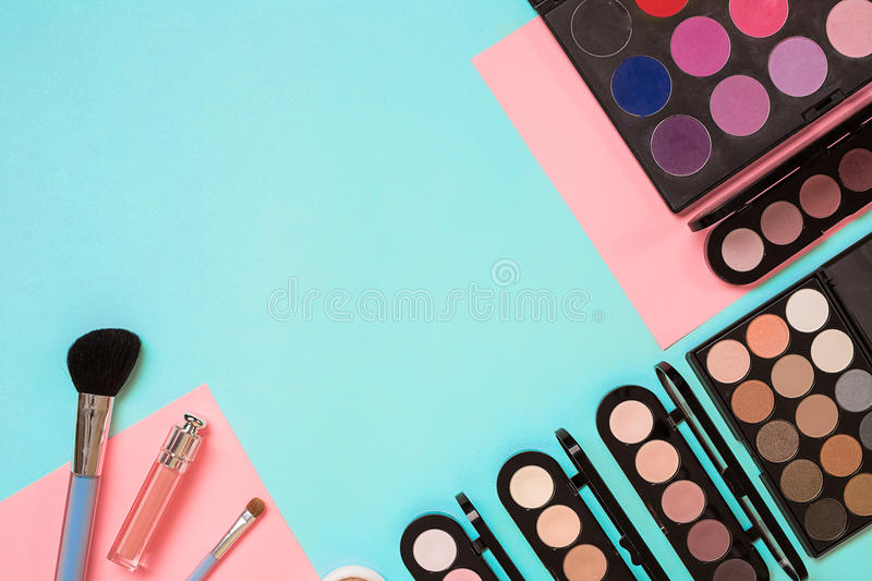 Make up essentials. Set of professional make up brushes, creams and shadows in jars on blue background. stock image