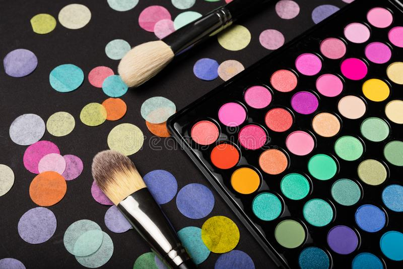 Make-up eyeshadow palette with brushes on back background with confetti. Close-up shot of make-up eyeshadow palette with two brushes on back background with stock photos