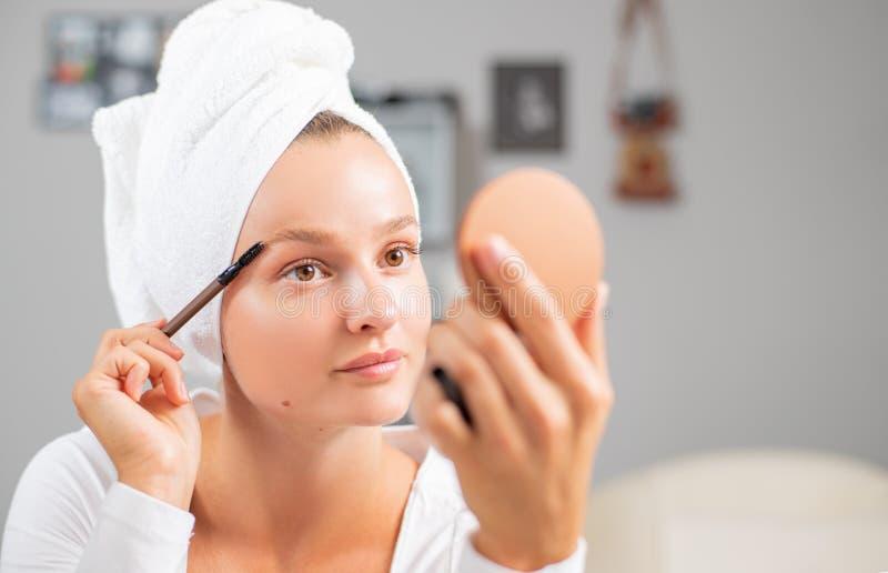 Make up. Girl apply make up on eyebrows stock photography