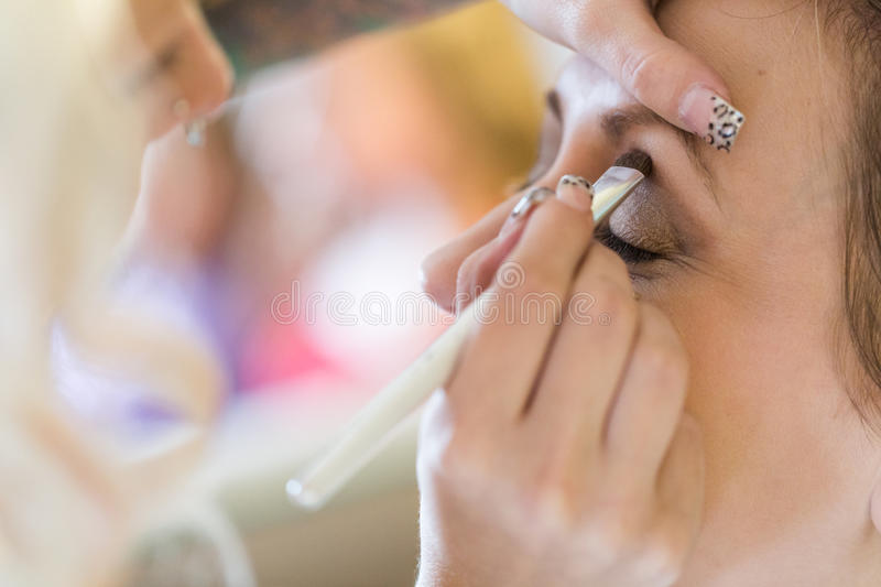 Make up. Makeup artist applying make up to the brides face royalty free stock photos