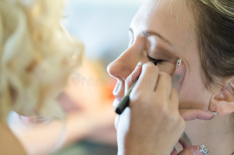 Make up. Makeup artist applying make up to the brides face royalty free stock images
