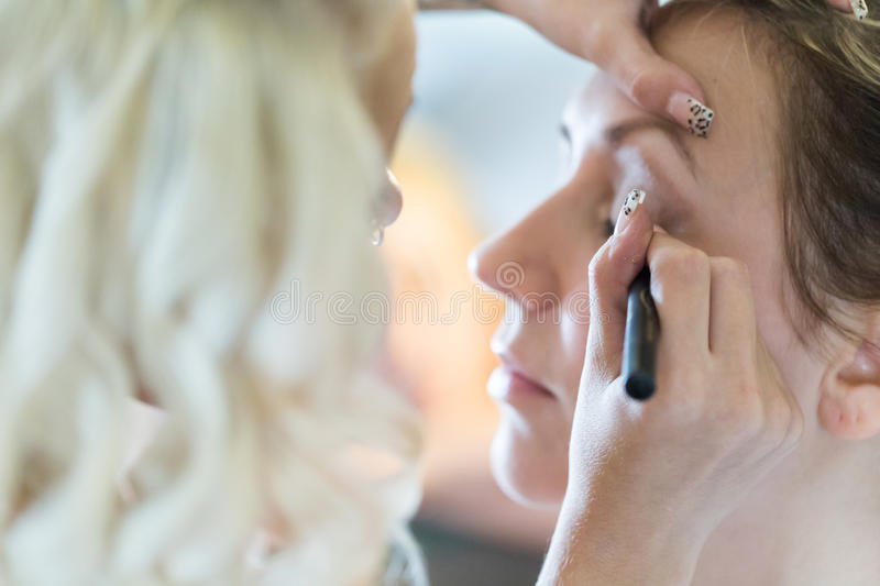 Make up. Makeup artist applying make up to the brides face stock image