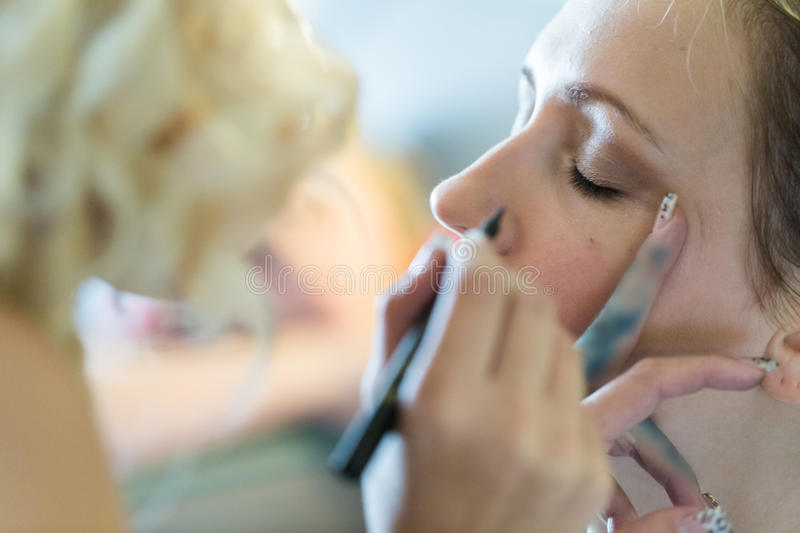 Make up. Makeup artist applying make up to the brides face stock photography