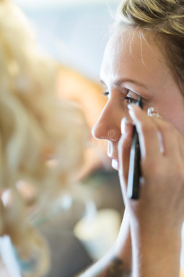 Make up. Makeup artist applying make up to the brides face royalty free stock photography