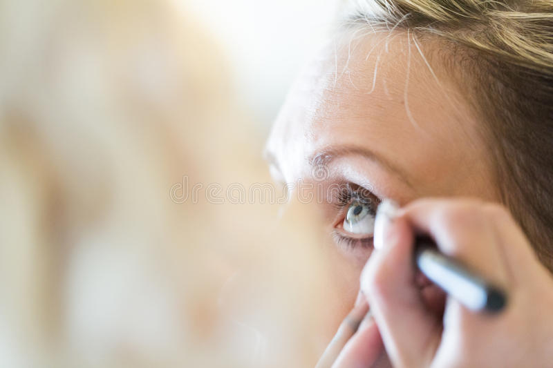 Make up. Makeup artist applying make up to the brides face royalty free stock photo