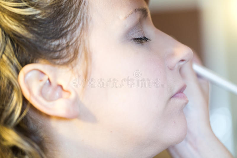 Make up. Makeup artist applying make up to the brides face stock photos