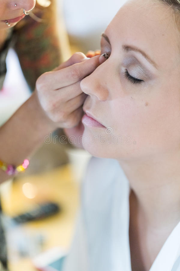Make up. Makeup artist applying make up to the brides face stock photo