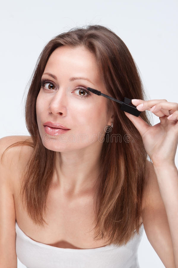 Make-up with mascara. Beautiful young woman with long eyelashes having makeup stock image