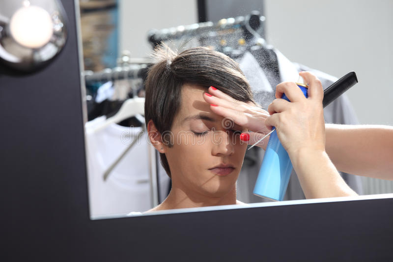 Make up model at mirror in dressing room, sprays hair spray. Make up man model at mirror in dressing room, sprays hair spray royalty free stock photography