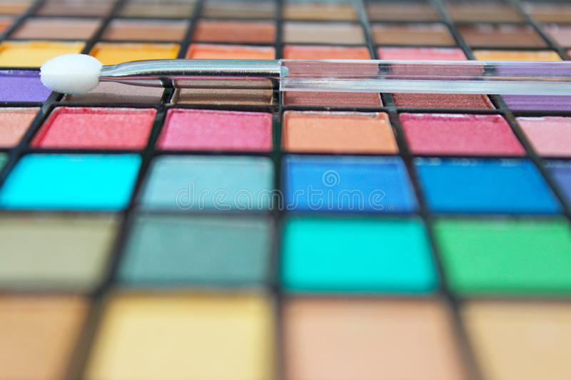 Make up palette and applicator. Vivid and colorful make up palette and applicator. Focus on the applicator wand stock image