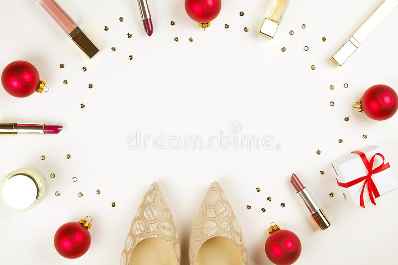 Make up products with Christmas decoration and golden womans shoes on white background with copy space flat lay stock images